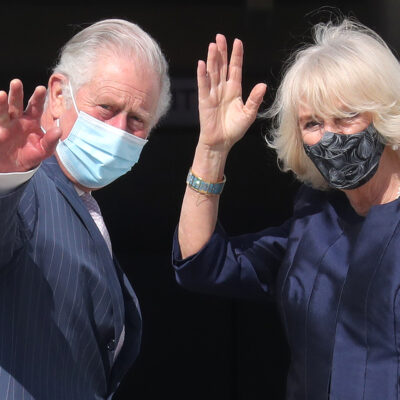 Prince Charles on the left, Camilla Parker Bowles on the right, waving and wearing masks.