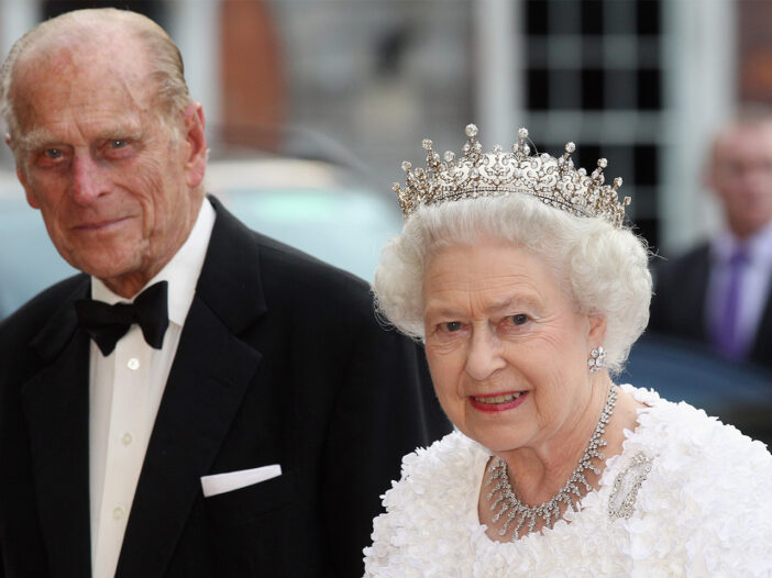 Prince Philip on the left in a tuxedo, walking with Queen Elizabeth, who's wearing a crown