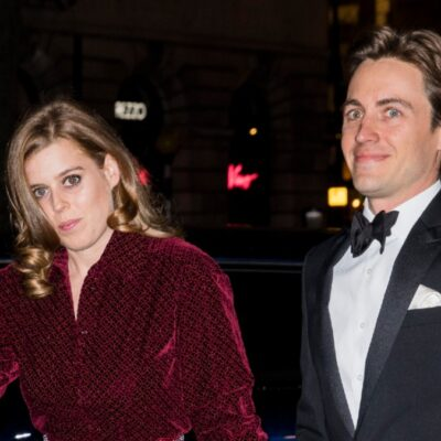Princess Beatrice, wearing a red dress, walks with her husband, Edo