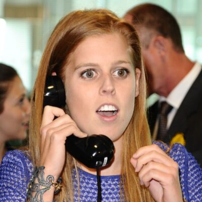 Princess Beatrice wears a purple dress as she mans the phones for a charity event