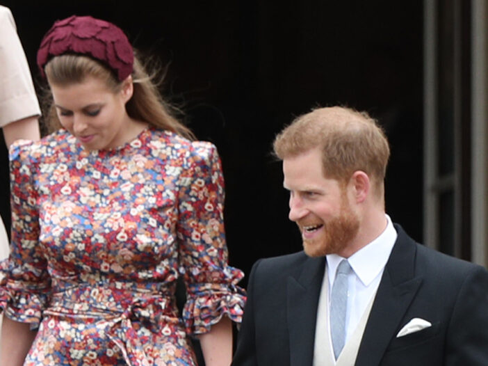 Princess Beatrice looking down on the left, Prince Harry on the right, laughing