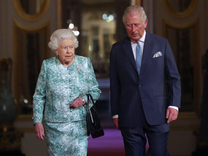 Queen Elizabeth on the right, walking down a hall with Prince Charles
