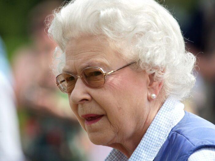 Queen Elizabeth wears a blue sweater vest as she greets a crowd