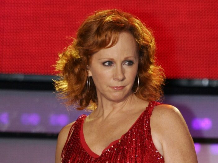Reba McEntire wearing a red dress on stage