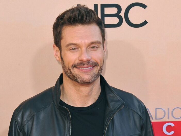 Ryan Seacrest wears a black leather jacket on the red carpet