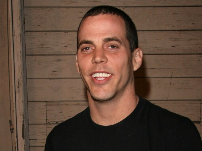 Steve-O wears a black t-shirt against a wooden background