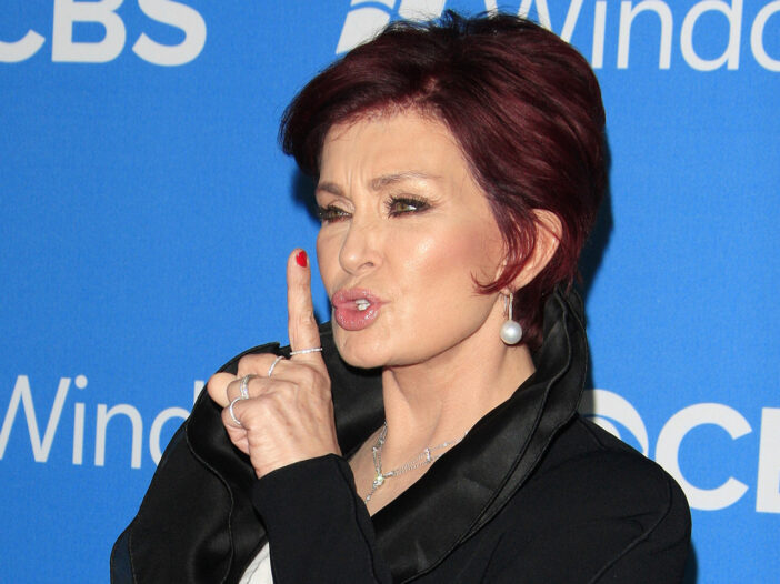"""Sharon Osbourne making a """"shhh"""" gesture with her finger to her lips"""