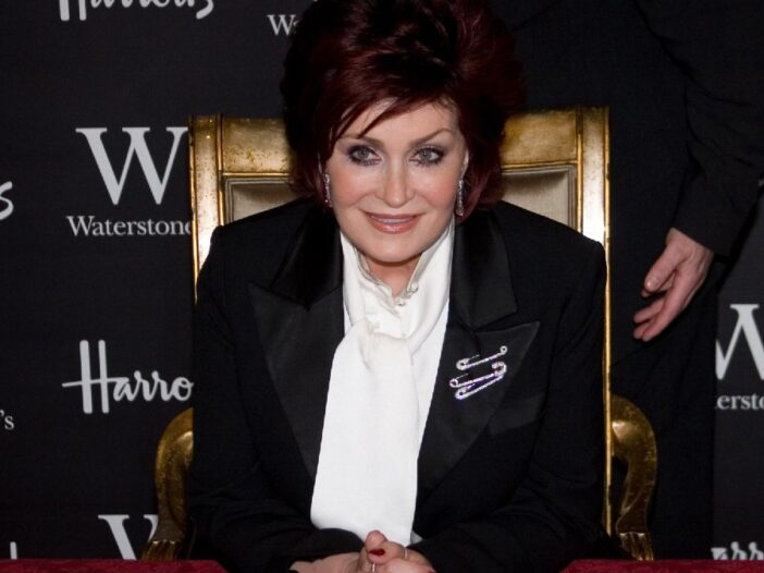 Sharon Osbourne wears a black suit jacket and white shirt as she sits in a golden chair at a red table