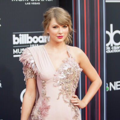 Taylor Swift in a peach dress with her hand on her hip