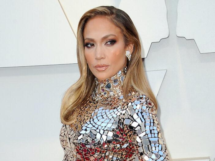 Jennifer Lopez looking back in a silver dress