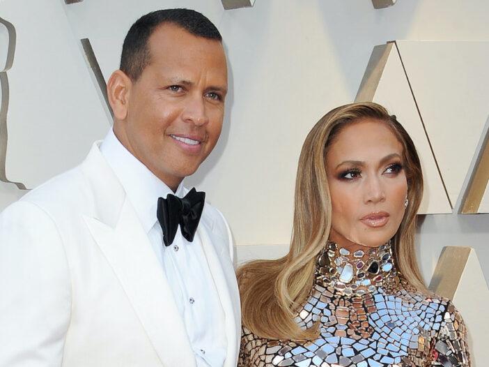 Alex Rodriguez in a white tuxedo with Jennifer Lopez in a silver dress