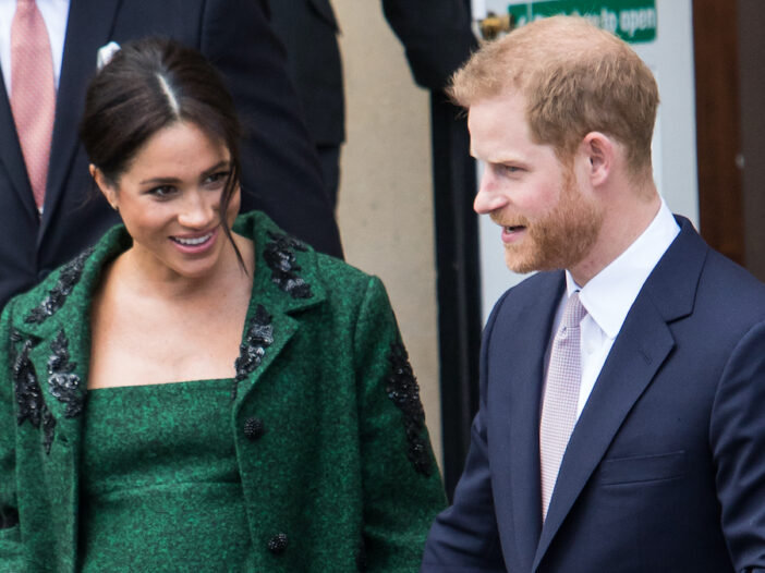 Prince Harry in a suit with Meghan Markle in a green dress