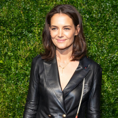 Katie Holmes smiling in a leather jacket