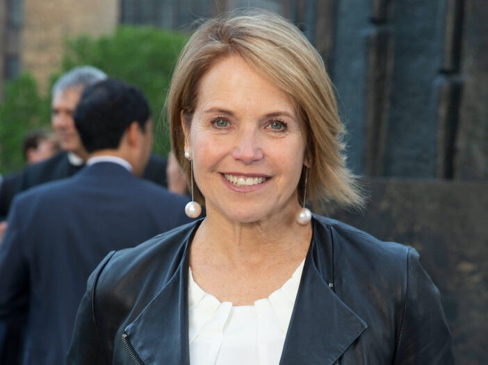 Katie Couric smiling in a leather jacket