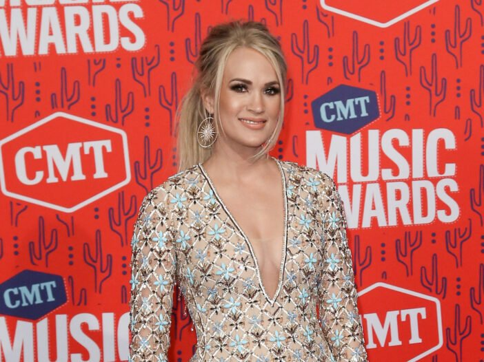 Carrie Underwood smiling in a tan dress