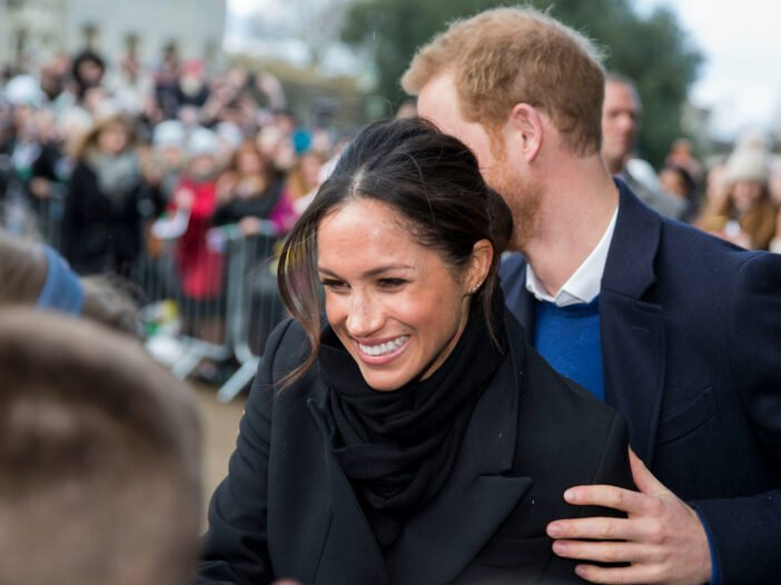 Meghan Markle smiling in a black coat with Prince Harry