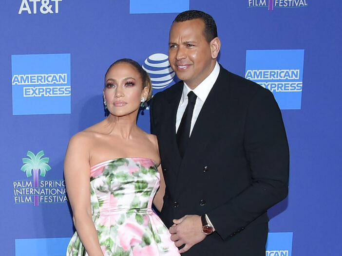 Jennifer Lopez in a floral dress with Alex Rodriguez in a suit