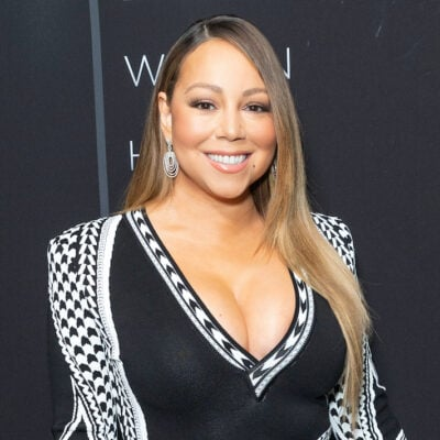 Mariah Carey smiling in a black and white outfit