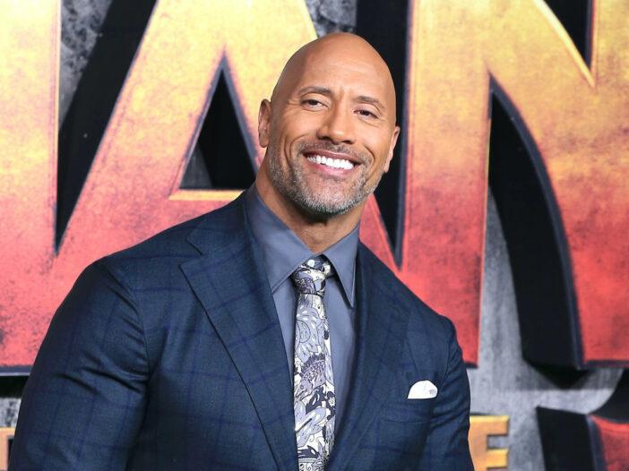 Dwayne Johnson smiles in a suit