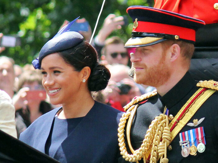 Meghan Markle smiling in a carriage with Prince Harry
