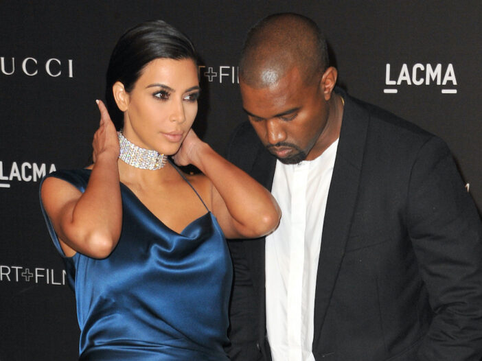 Kim Kardashian in a blue dress with Kanye West in a suit