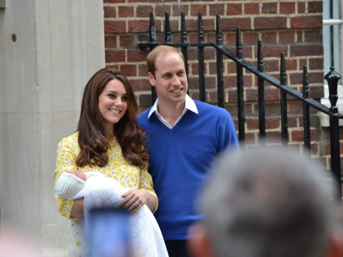 Kate Middleton and Prince William holding baby Charlotte during a press event.