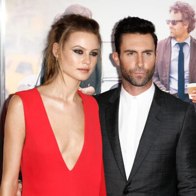 Behati Prinsloo in a red dress and Adam Levine in a black suit at a red carpet event.