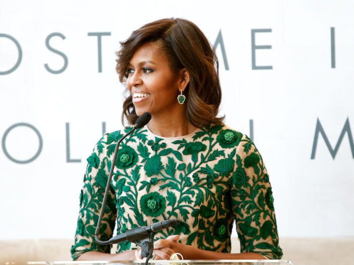 Michelle Obama smiling in a green dress