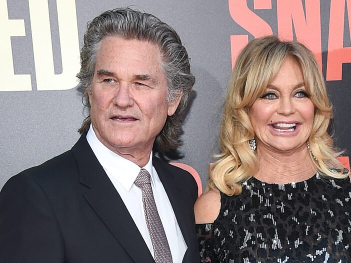 kurt russell in a suit with Goldie Hawn in a black dress