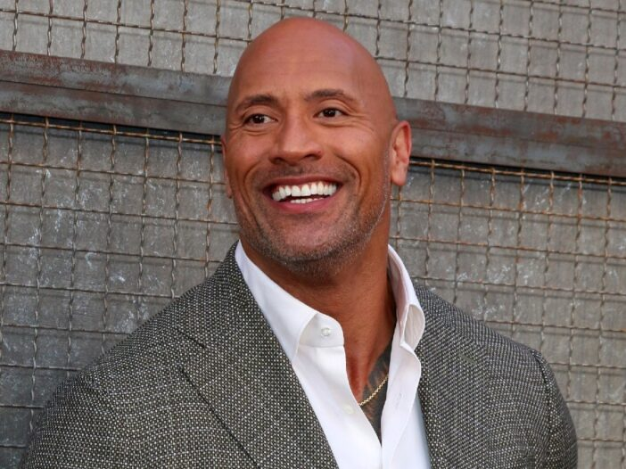 Dwayne The Rock Johnson wears a gray suit against a gray wall