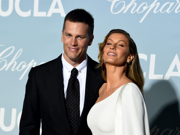 Tom Brady on the left in a suit, Gisele on the right in a white dress, looking up dramatically