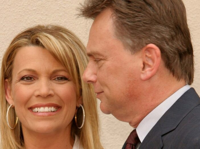 Vanna White and Pat Sajak stand closely together in front of a beige backdrop