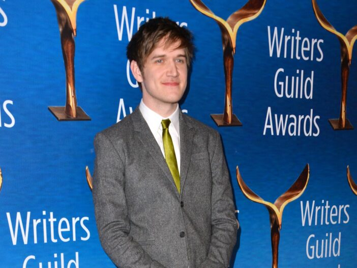 Bo Burnham smiling at the camera and wearing a grey suit with a green tie.