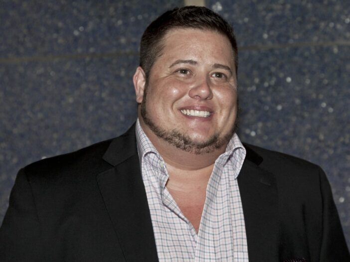 Chaz Bono smiling and wearing a black blazer with a white shirt.