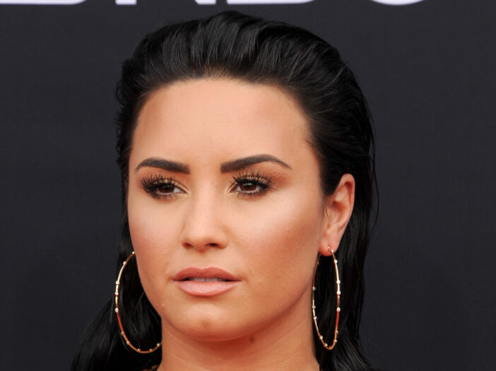 Demi Lovato sporting a slicked back hairstyle and hoop earrings