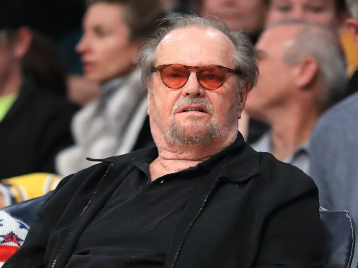 Jack Nicholson in a black outfit with orange sunglasses courtside