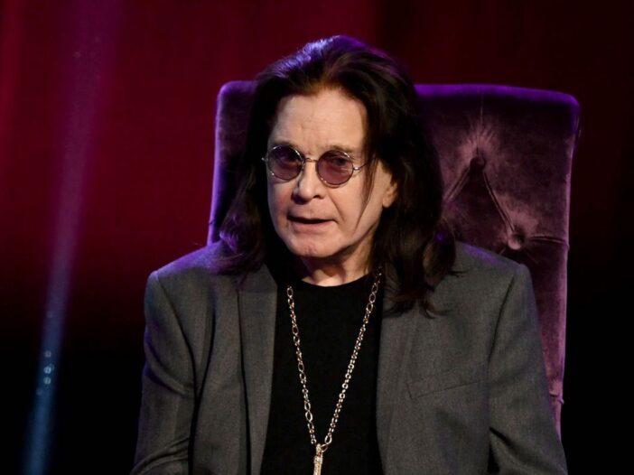 Ozzy Osbourne in a grey suit sitting down
