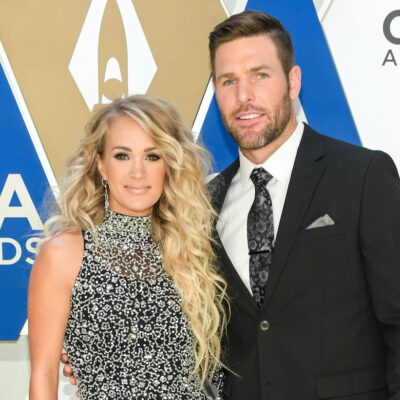 Carrie Underwood in a patterned dress with husband Mike Fisher in a suit