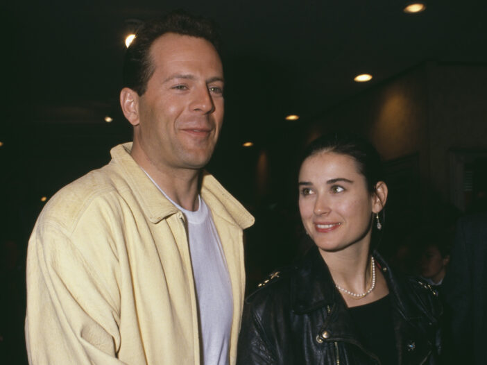 Bruce Willis in a yellow shirt with Demi Moore in a jacket