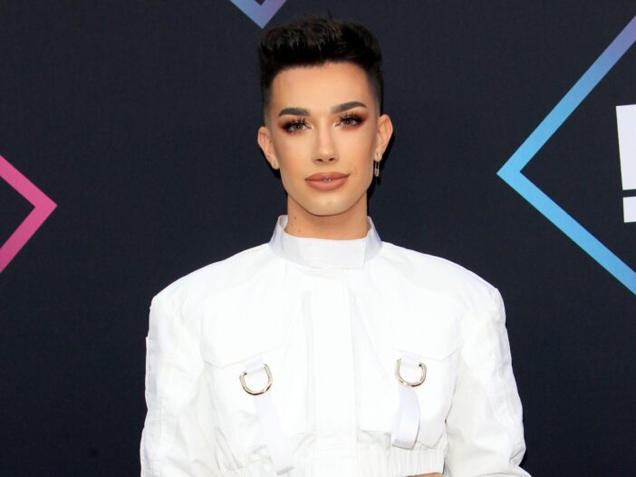 James Charles wearing a white jacket.
