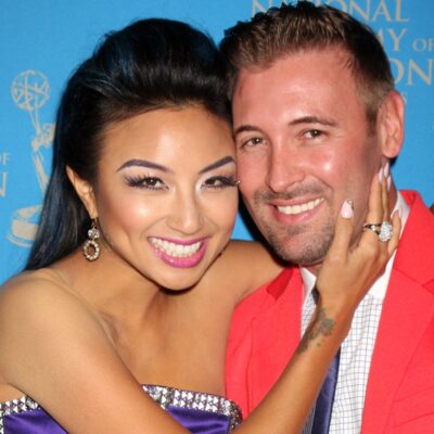 Jeannie Mai in a purple dress with her arms around Freddy Harteis, who is wearing a red suit.