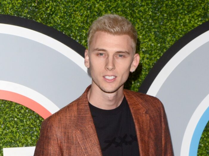 MGK smiling and wearing a red suit with a black shirt.