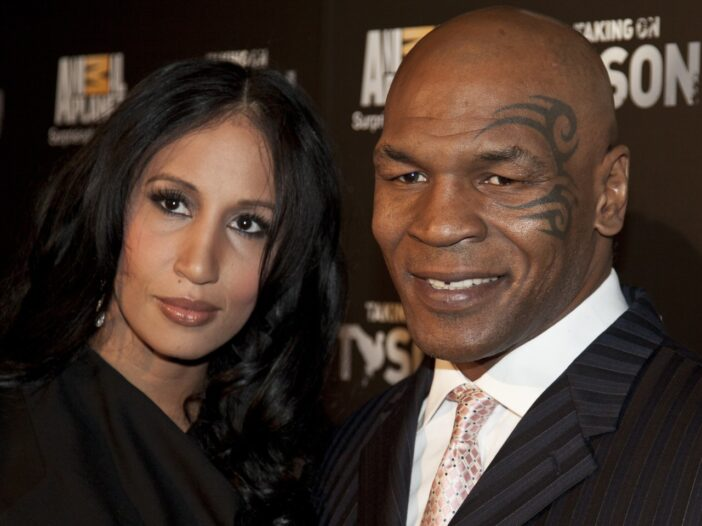 Mike Tyson and his wife, Lakiha Spicer, are standing close and smiling at the camera. Mike is wearing a black, striped suit, and Lakiha has dark curly hair and is wearing a black dress.