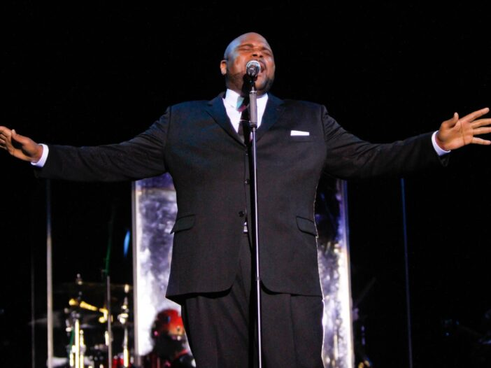 Ruben Studdard performing and wearing a black suit with his hands in the air.