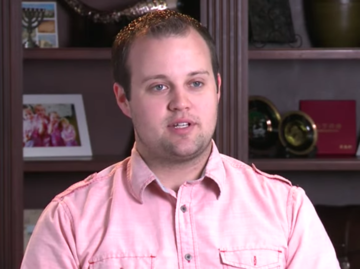 Josh Duggar wearing a pink button-down shirt during a confessional on 19 Kids and Counting