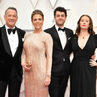 The Hanks Family is posing together at the Oscars. Tom and Truman Hanks are both wearing black tuxedos, Rita Wilson is wearing a pink dress, and Elizabeth Ann Hanks is wearing a black dress.