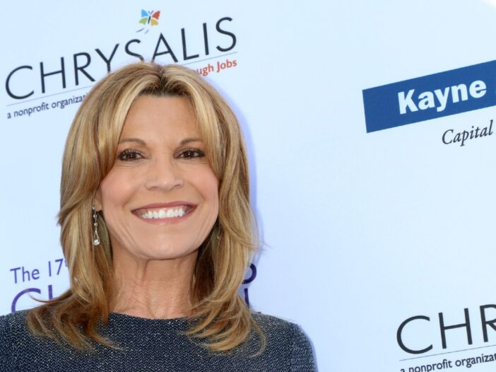 Vanna White smiling and wearing a grey dress.