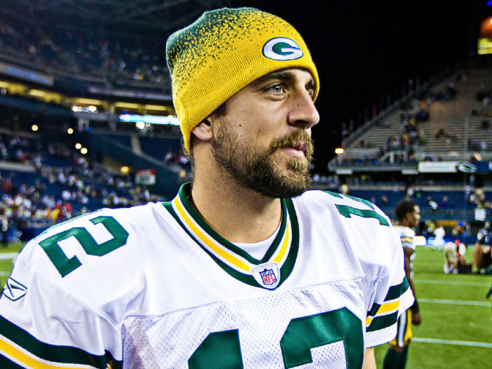 Aaron Rodgers wears his Green Bay Packers uniform and stares off camera