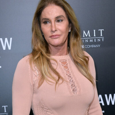 Caitlyn Jenner in a pink dress in front of a gray background