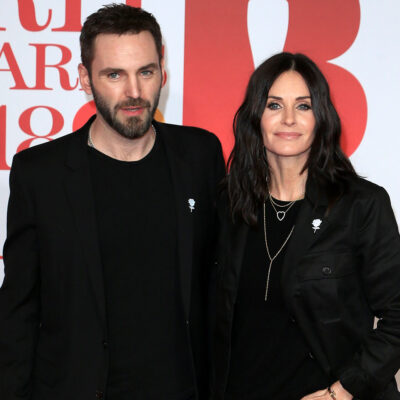 Johnny McDaid on the left, Courteney Cox on the right, both wearing black